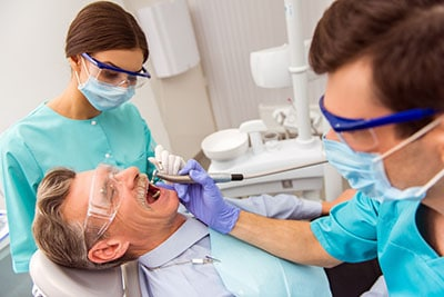 Young dentist and his assistant treating elderly man
